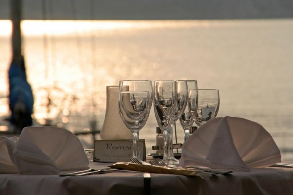 A dinner table set right on the Lake. There are 3 water classes and 3 champagne glasses. The napkins are folded in a fan fashion and there is a reserved sign on the table leaning up against a candle vase. Everything from the table clothes to the linens are drapped in white, the lake is in the background.