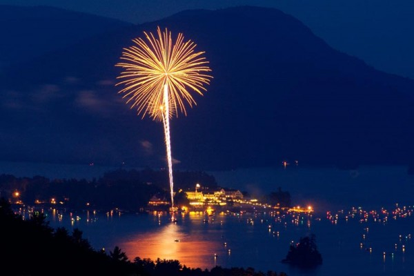 A large firework is going off with one small one below it, they are both in am amber hue. There are numerous boats on the dark lake that are lit up. The mountains are in the background and the town is lit by the buildings.
