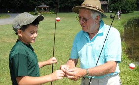 An elderly man to the right weraing a hat and light blue polo is helping a young boy, on the left, wearing a green shirt and baseball hat tie fishing line. They are both holding fishing poles with red and white bobbers on them. To the right you can see part of the pond, and in the background is the gazebo and 2 other men fishing.