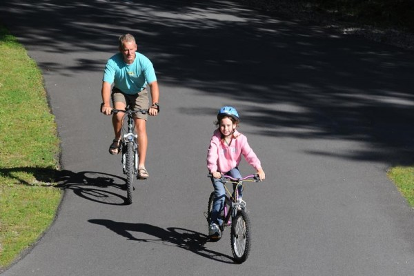 Dad & Daughter riding their bikes down East West Blvd towards the East Building all smiles on a beautiful summer day