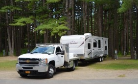 A white pick up truck attached to a travel trailer, backing it into a site on the east end. There are pines trees in the background and the street in front of the truck.
