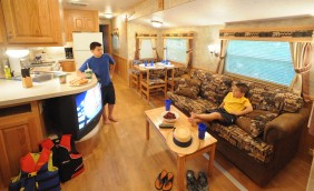 Two boys relaxing in an onsite rental unit. One boy is sitting on the couch while the other is standing next to the tv. Around the RV you can see life jackets, hats, sandals and food!