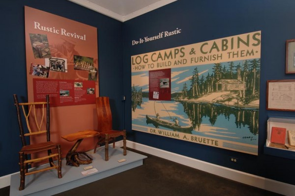 Inside one of the many local museums. To the left is the rustic revival section showing two chairs made of wood with a table inbetween. In the middle is a poster in regards to 'Log Camps & Cabins'.