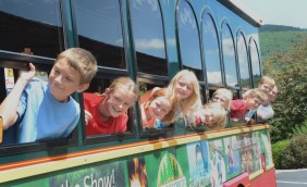 9 Lake George RV Park guests of all different ages with their heads out the window of the trolley smiling for the camera.