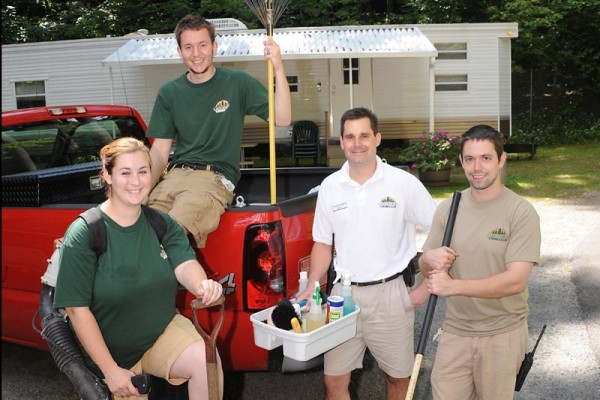 Our janitorial services crew in front of one of our onsite rental units. The supervisor Tim is in a white shirt and khakis, while 2 employees are wearing green t shirts and khakis and the other male wearing a khaki shirt with khaki shorts. One male is sitting in the red truck while the other 3 are standing.