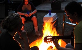 A young couple sitting fireside outside one of our onsite rental units. The teenage girl to the left is looking at the boy to her right playing guitar. There is another teenage boy in the background sitting in a chair watching the fire.