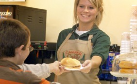 A Lake George RV Park camper cafe employee hand a breakfast sandwhich to a young boy down at the camper cafe.