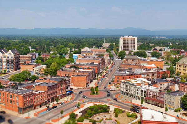 An overview of downtown Glens Falls, NY. There is a traffic circle in the middle with a park in the foreground. There are numerous buildings and the mountains are in the background.