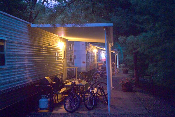Patios of our onsite rental units. There are multiple bikes stored under the awning and a gas Weber grill to the left. The lights are on as it is currently dark outside.