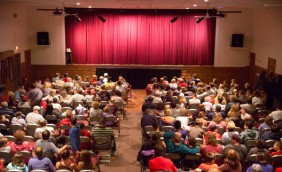 French Mountain Playhouse theatre filled to capacity. Every seat is taken with guests anxiously awaiting the performance. The curtain is drawn and lighted as the show is about to begin.