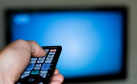 A blurry TV in the background with a hand to the left holding a remote in the foreground in focus.