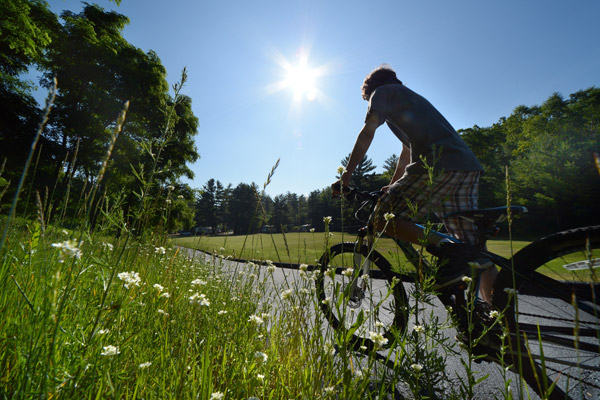 A teenage boy riding his bike on our paved bike trails. There are white flowers in the foreground and not a cloud in the sky with the sun shining brightly.