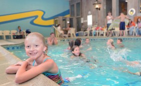 A young girl with her arms leaning on the side of the indoor pool, her body is in the water. Shes smiling for the camera. There are multiple other guests in the background swimming behind her. There are also many people outside the pool sitting in the chairs.