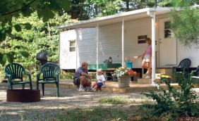 One of our onsite rental units there is a gas weber grill, picnic table with checked green table cloth, and 2 green chairs around a set unlite campfire. There is a family of 4 on the patio a dad, mom and their young son and daughter.