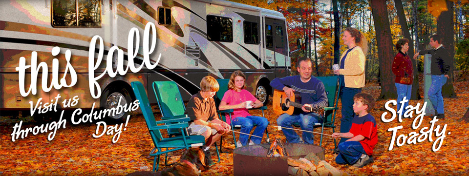 A family of 5 sitting around a campfire. The 3 young children are roasting marshmallows while the father is playing guitar. The mom is standing next to the father's chair holding a cup of coffee. There is an RV in the background and orange leaves line the ground. In the back right hand corner there is another couple.