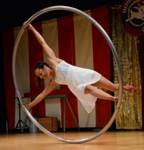French Mountain Playhouse artist Bindlestiff Family Cirkus, has a female performer in the middle of a large metal ring rolling around on stage.