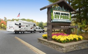 Entrance to Lake George RV park with entry sign with flowers underneath and a pick up truck pulling a 5th wheel entering the park