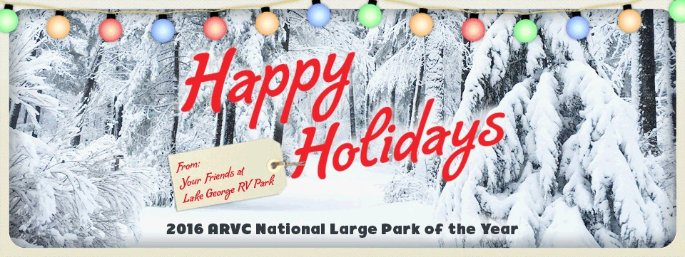 Snowy scene of pine trees covered in snow, happy holidays from the lake george rv park with holiday lights draped across the top of the image