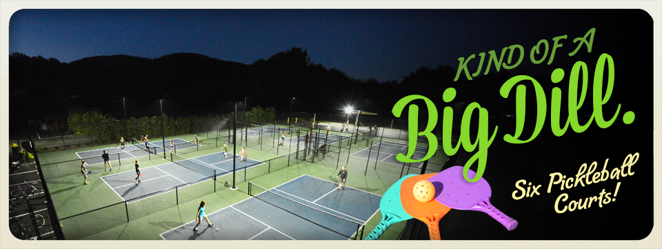 Numerous guests of all ages playing pickleball in the evening under the lights