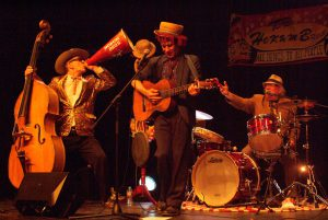French Mountain Playhouse artist, the Hokum Brothers. There are 3 of them 2 of them are standing, one playing guitar and the other bass while speaking into a megaphone. The 3rd brother is sitting and playing the drums. They are all dressed in casual suits and wearing hats.