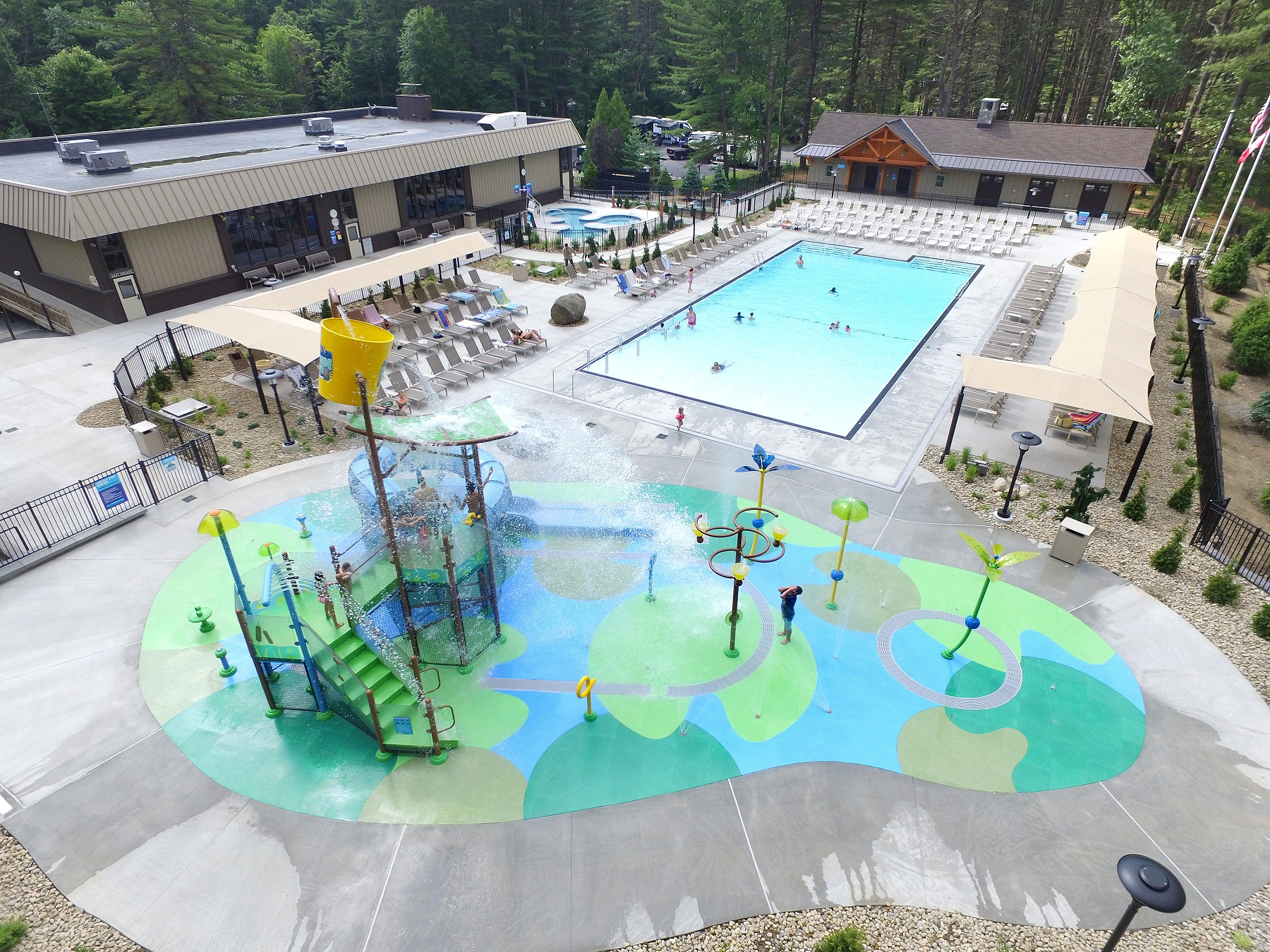 In the foreground the splash pad area is shown with children playing on the equipment. Behind the Splash Pad the zero entry pool is shown with people swimming in it and lounging in the chairs around it. In the far left of the photo the hot tub area is shown.