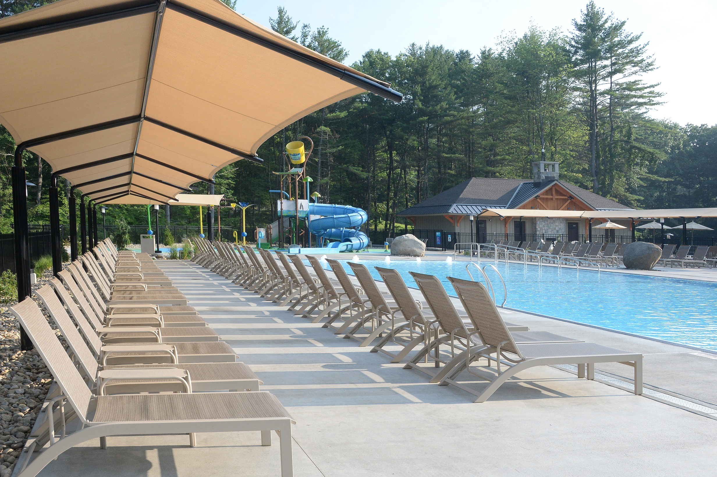 In the foreground the chairs are shown in two rows.  The back row is under a large shade and the front row is out in the sun. In front of the chairs the pool is shown.  In the background of the photo the splashpad area including the slide and dump bucket are shown. In the far right corner the Cascade Cove Bathroom facilities are shown.