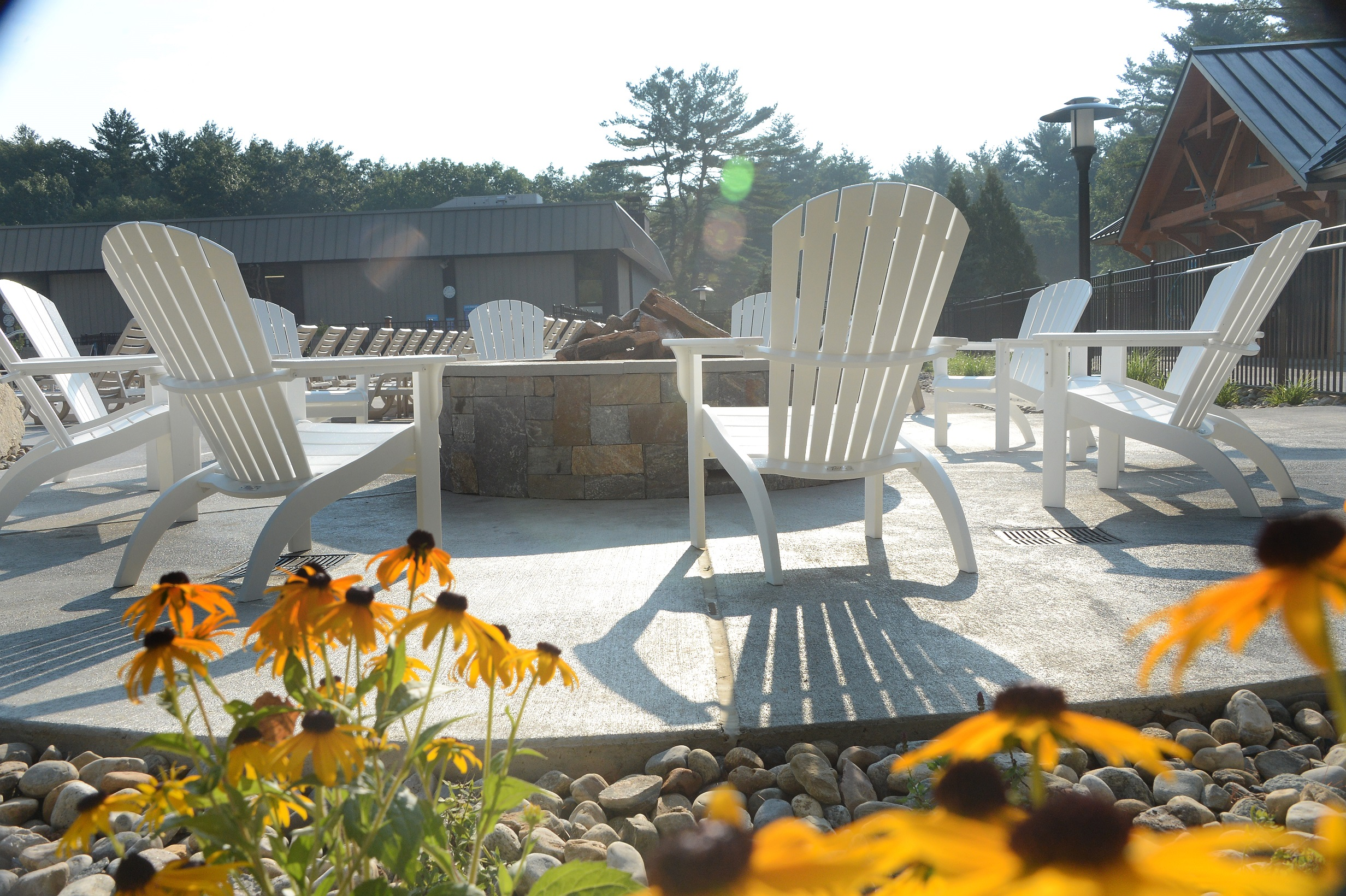 In this photo there is adirondack chairs surrounding a stone fire pit. Wood is stacked in the fire pit for the fire. Surrounding this area there are stones and flowers.