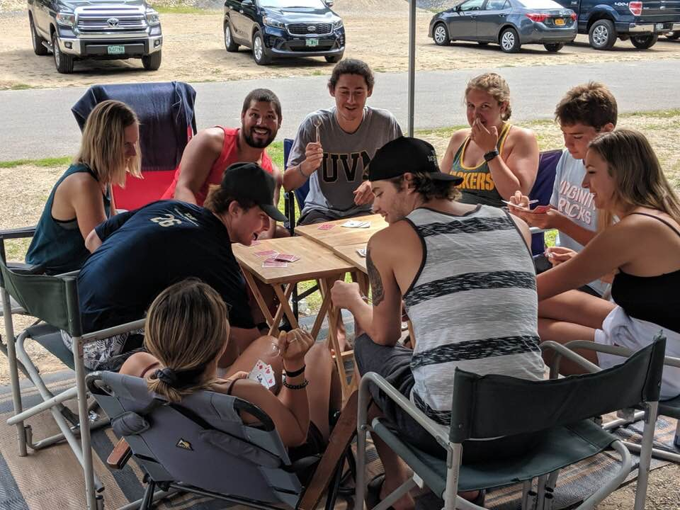 group gathered around table playing cards