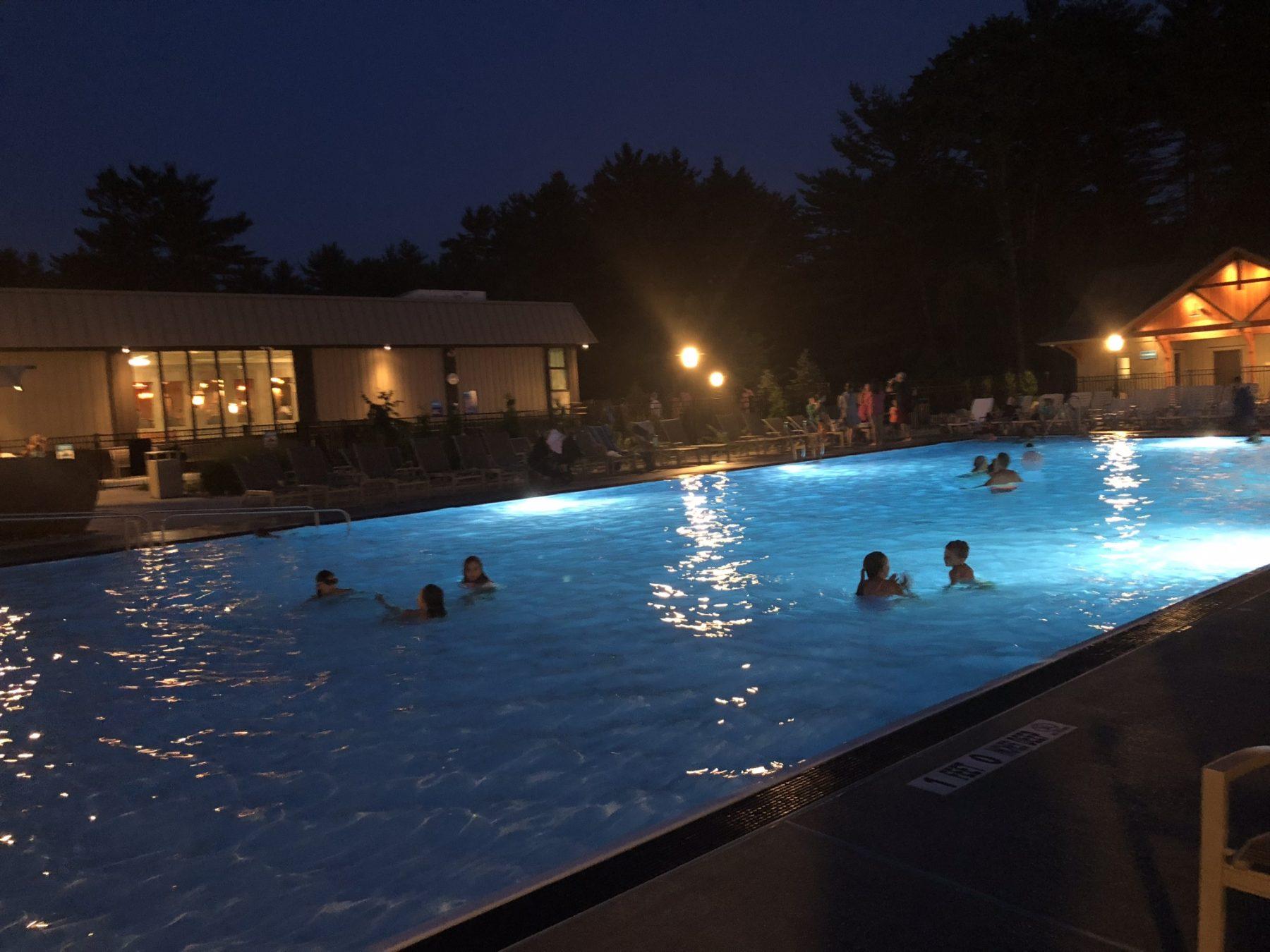 people swimming in pool a night