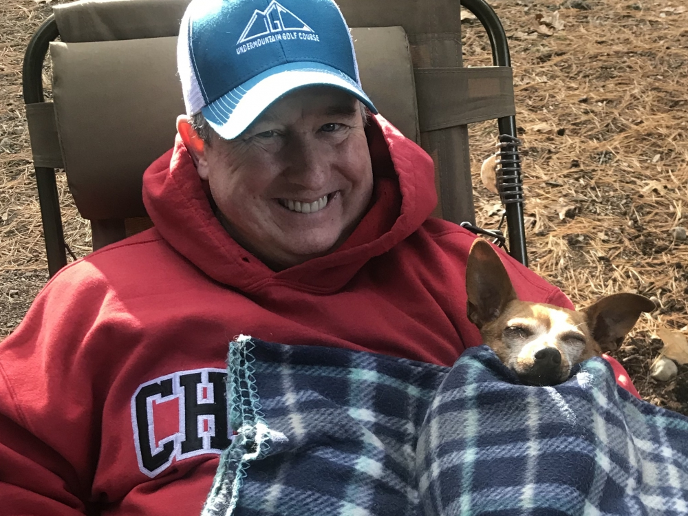 Man in lawn chair with small dog under blanket
