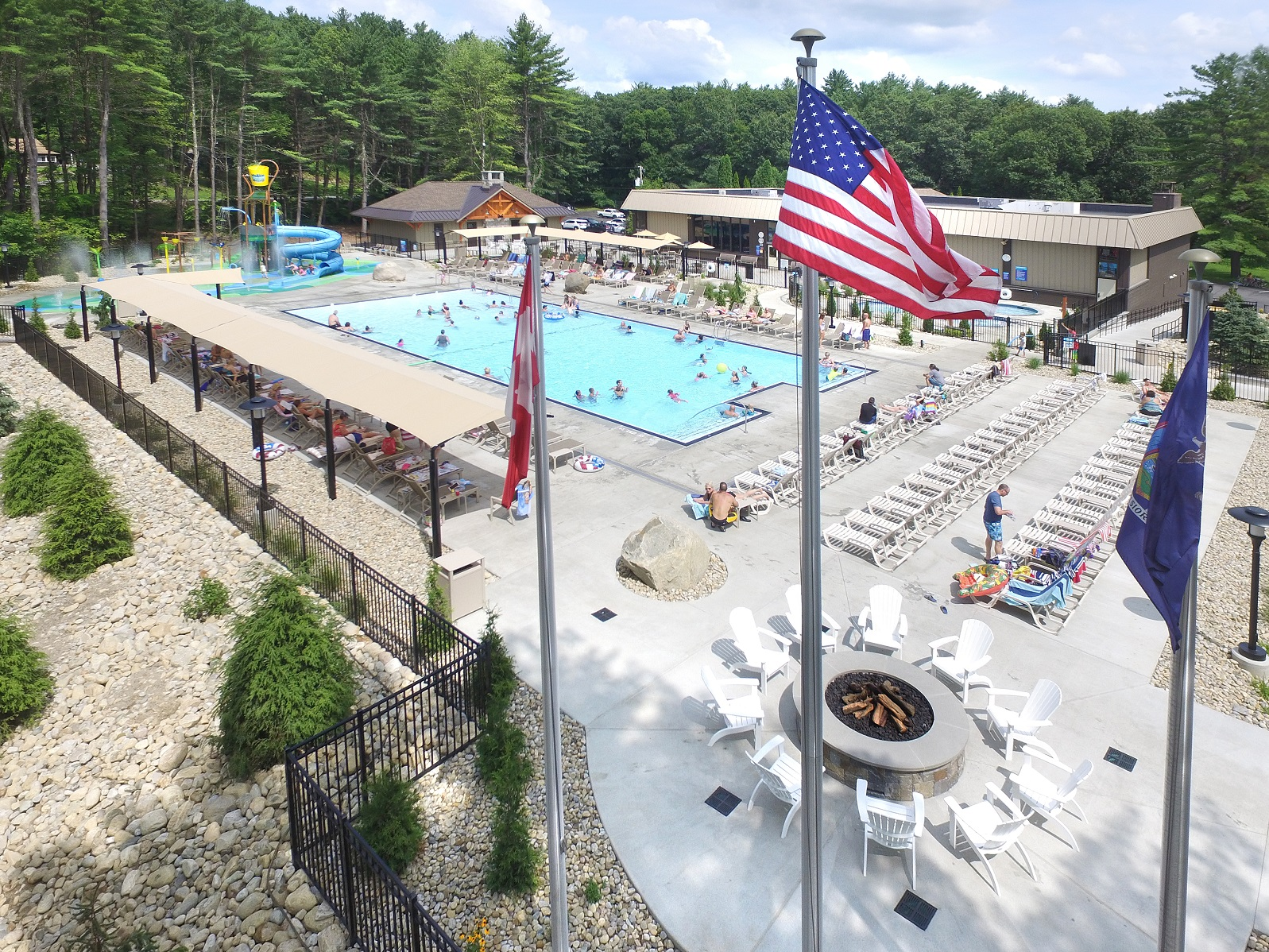 aerial view of Cascade Cove Aquatic Park and bonfire area on pool deck, American and Canada flags blowing in wind in forground