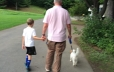 Dad and son walking dog