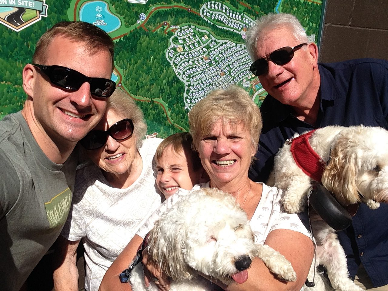 Family with dogs in front of map