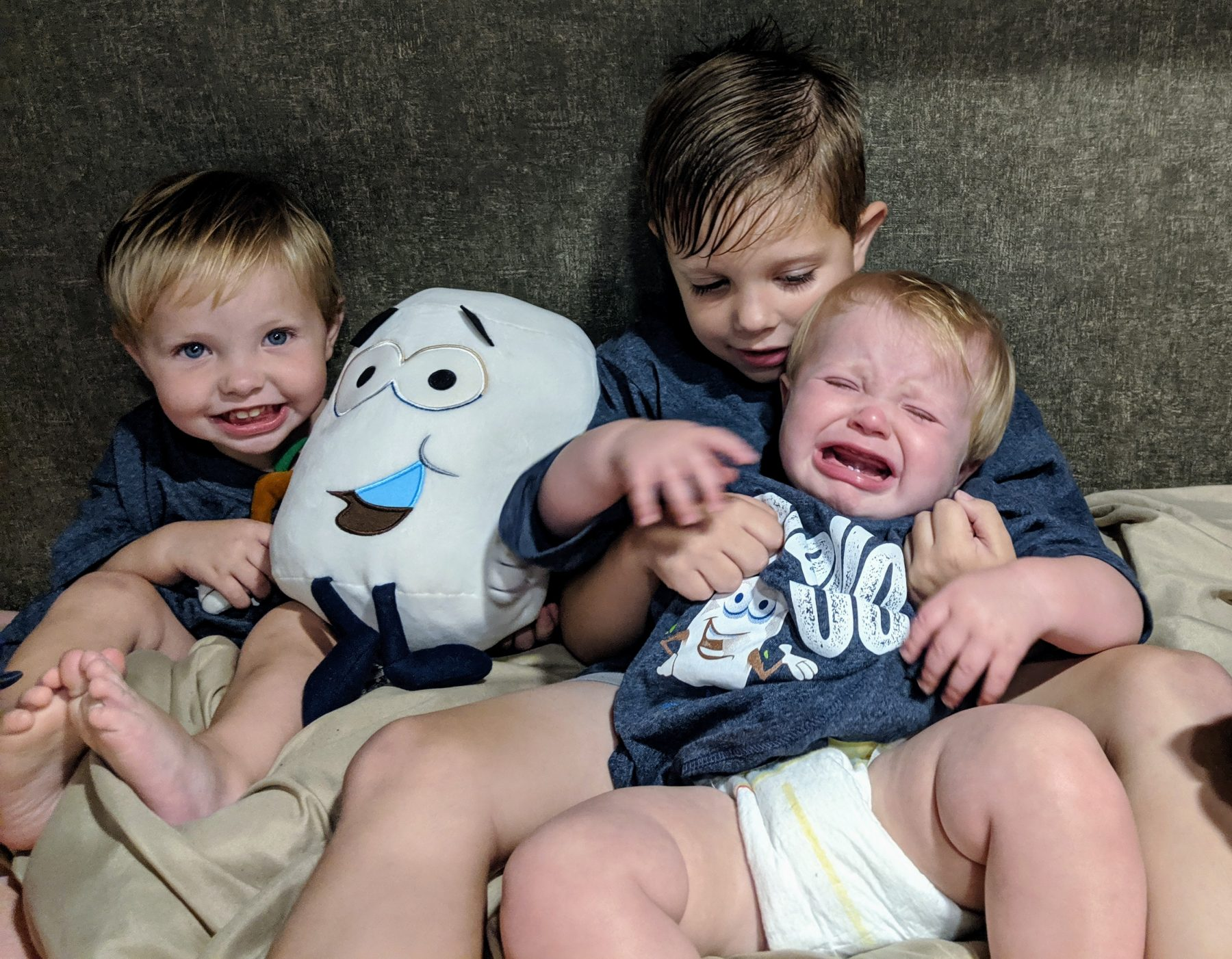 Young kids holding crying baby