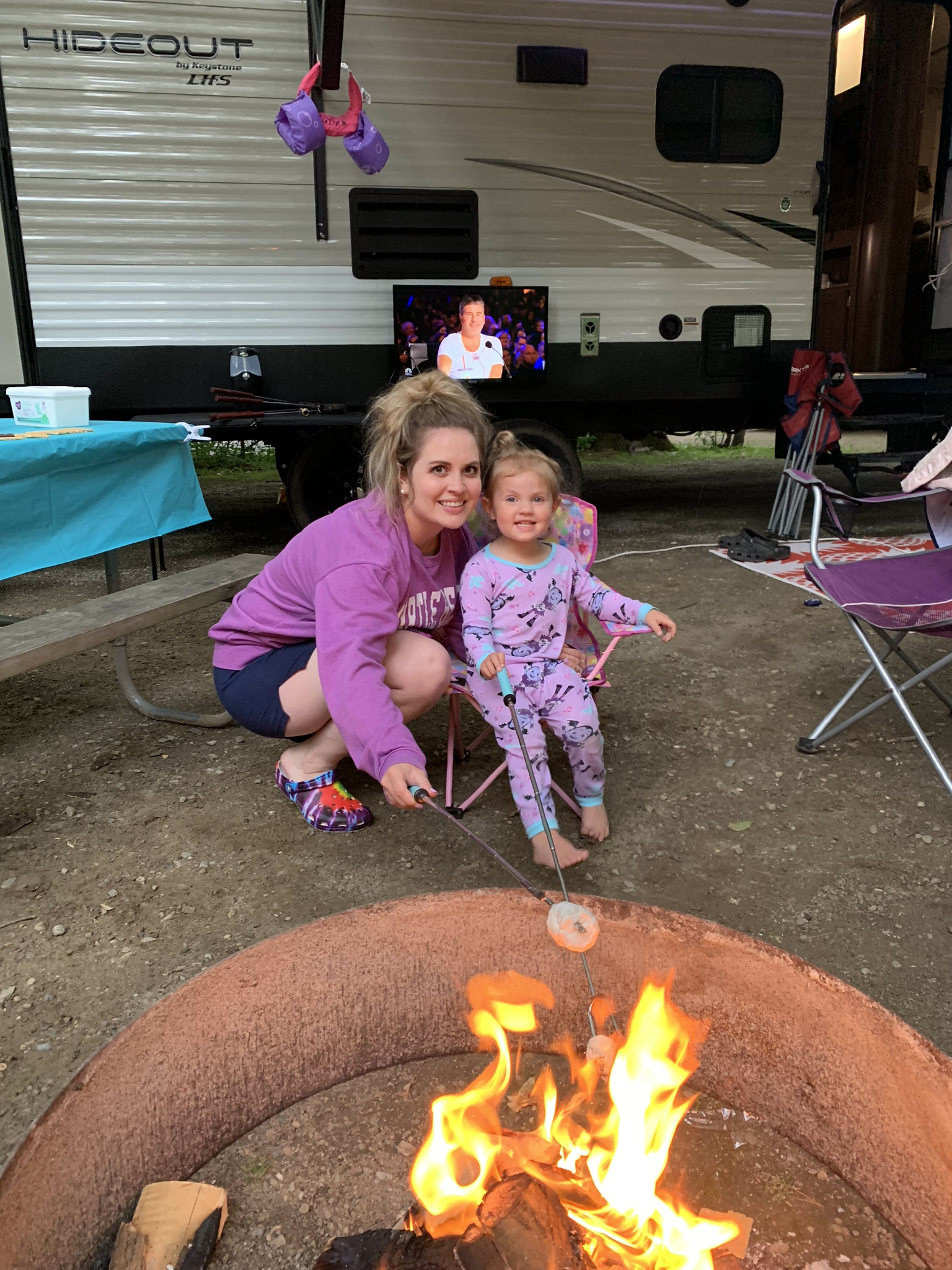 Family in front of fire with Smore smiles