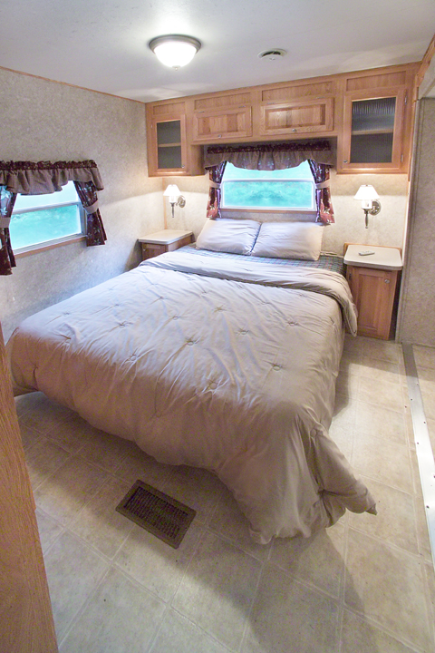 The master bedroom has a queen size bed with TV and ample storage space