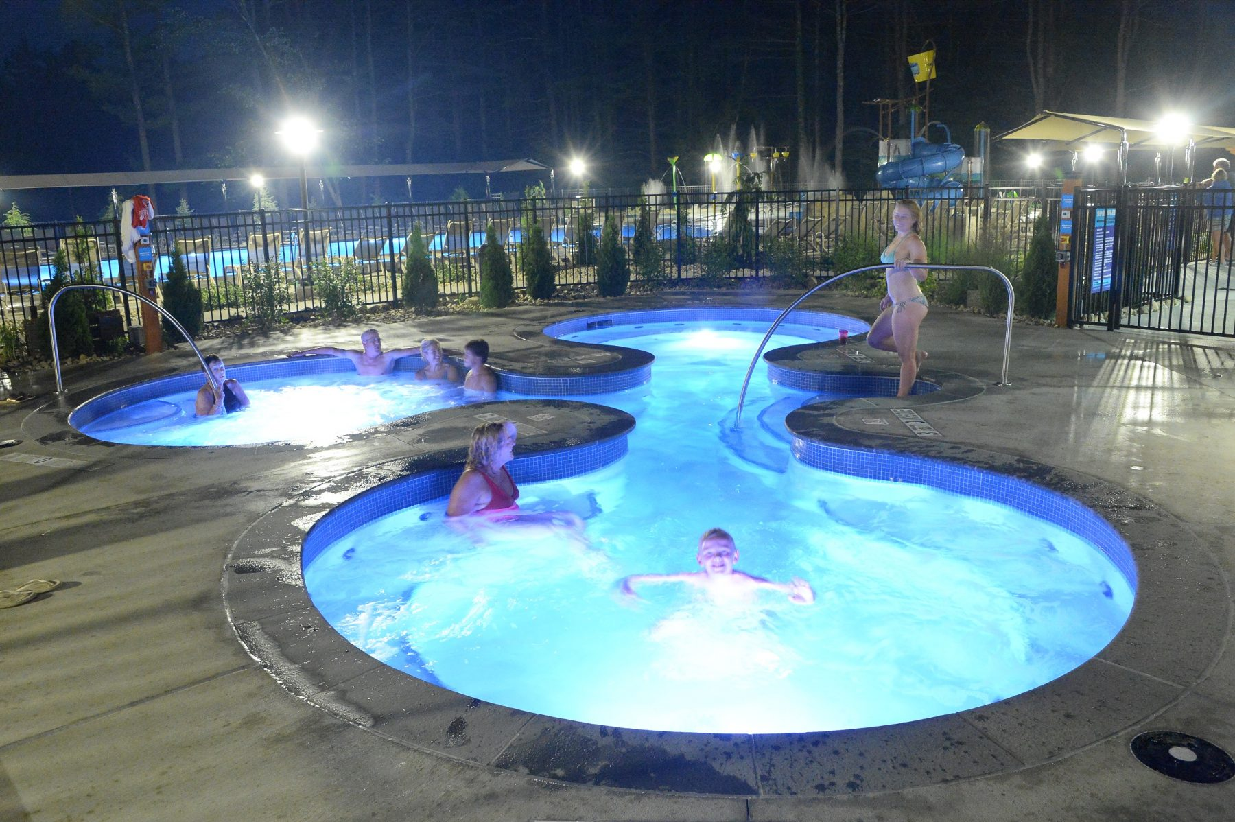 In the foreground the hot tub area is shown at night with guests lounging in it.   In the background the dump bucket and slide of the splash pad area is shown.