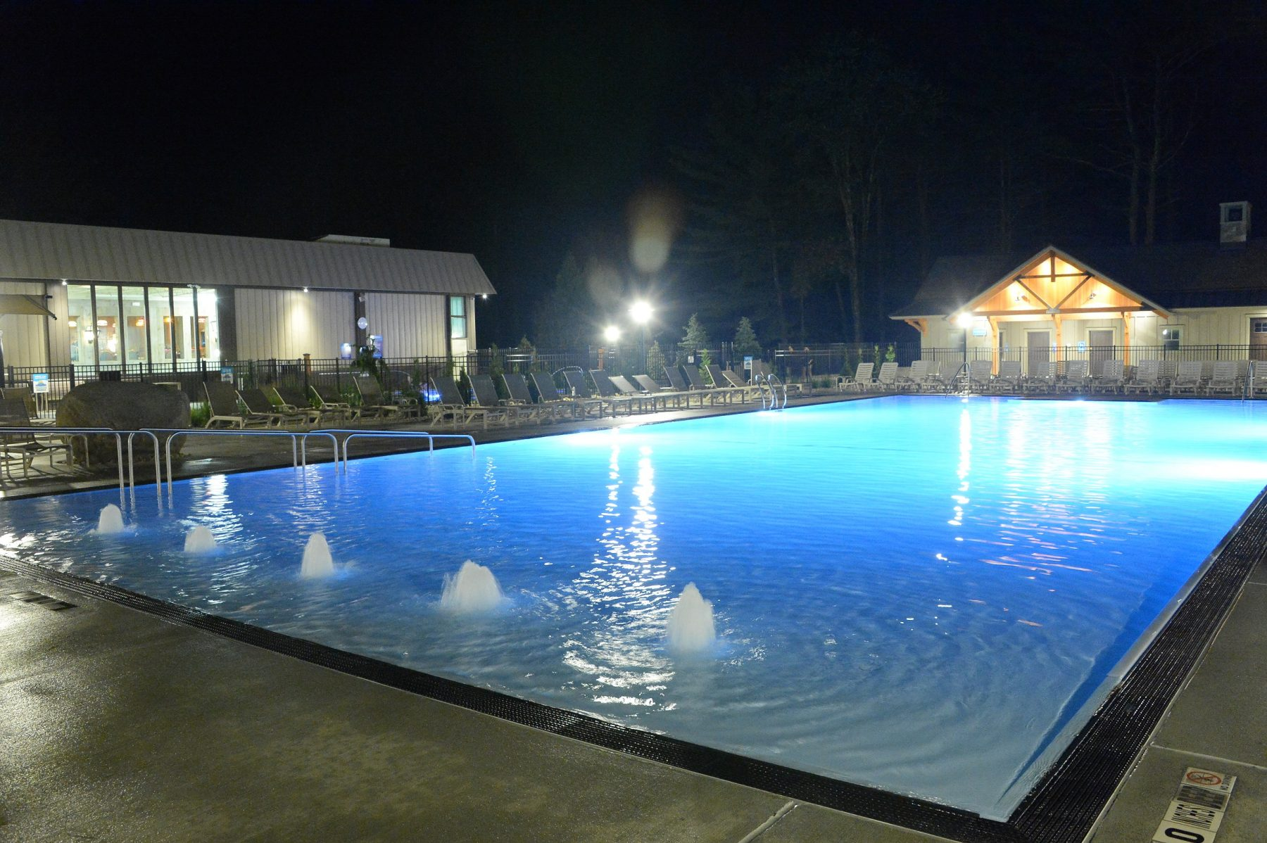 The zero entry pool is shown at night in the foreground. The east building and bathrooms are shown in the background.