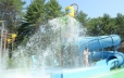 In the foreground of this photo the bottom of the slide is shown. Behind the slide there is a young woman being sprayed by the various sprayers. The dump bucket is shown upright at the top of the photo in the center. To the right side of the photo the enclosed slide is shown.