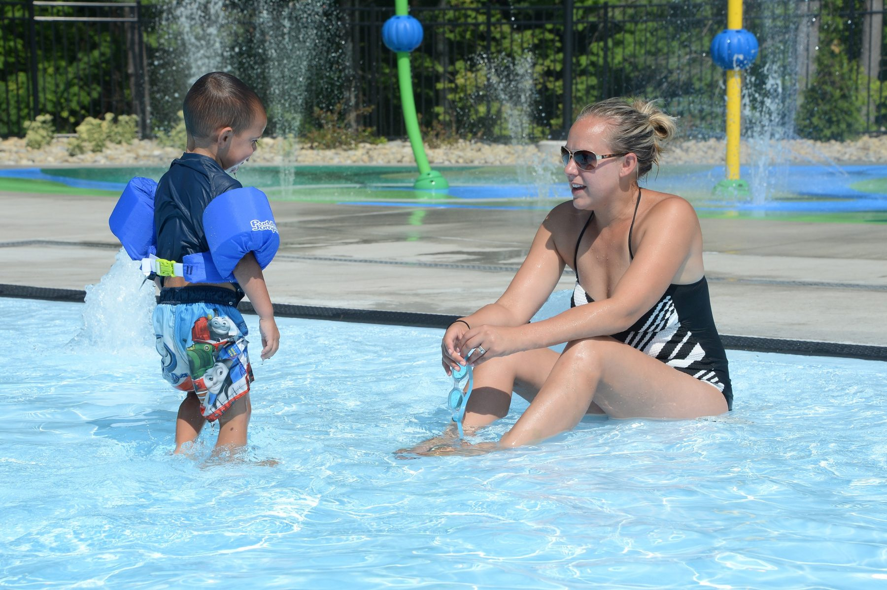 A woman is sitting in the entry area of the pool facing a young little boy who is standing in the entry of the pool. In the background some of the sprayers on the splash pad are shown.