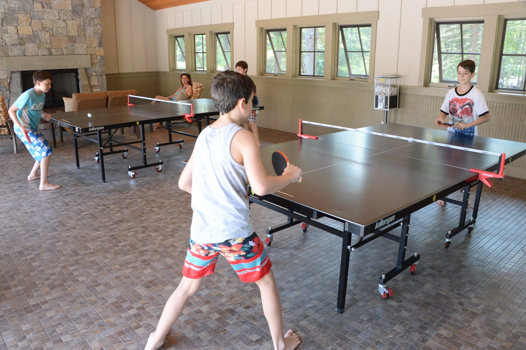 In the foreground of this photo both ping pong tables are shown. They are both being occupied by young boys playing ping pong.  In the background of the photo a young woman is shown sitting in one of the chairs watching the boys play.