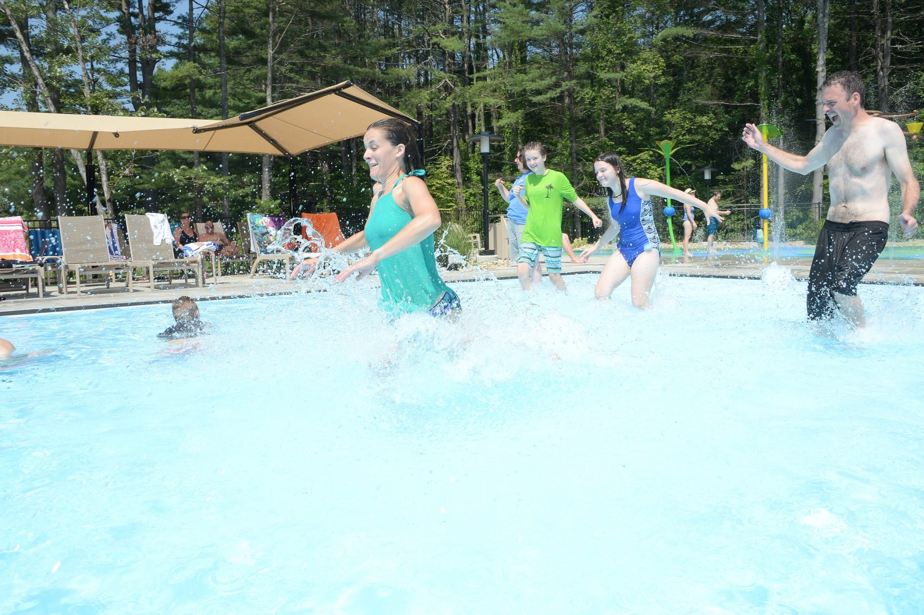 In the foreground of the photo a woman is shown running into the zero entry pool.  In the background of the photo a man accompanied by a young boy and a young girl are shown running into the pool. To the far left of the photo guests are shown lounging in the shaded area on the pool deck.