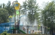 Splash pad with blue twisting slide, spray features, large yellow dump bucket, multiple children climbing steps up to slide, surrounded by black fence