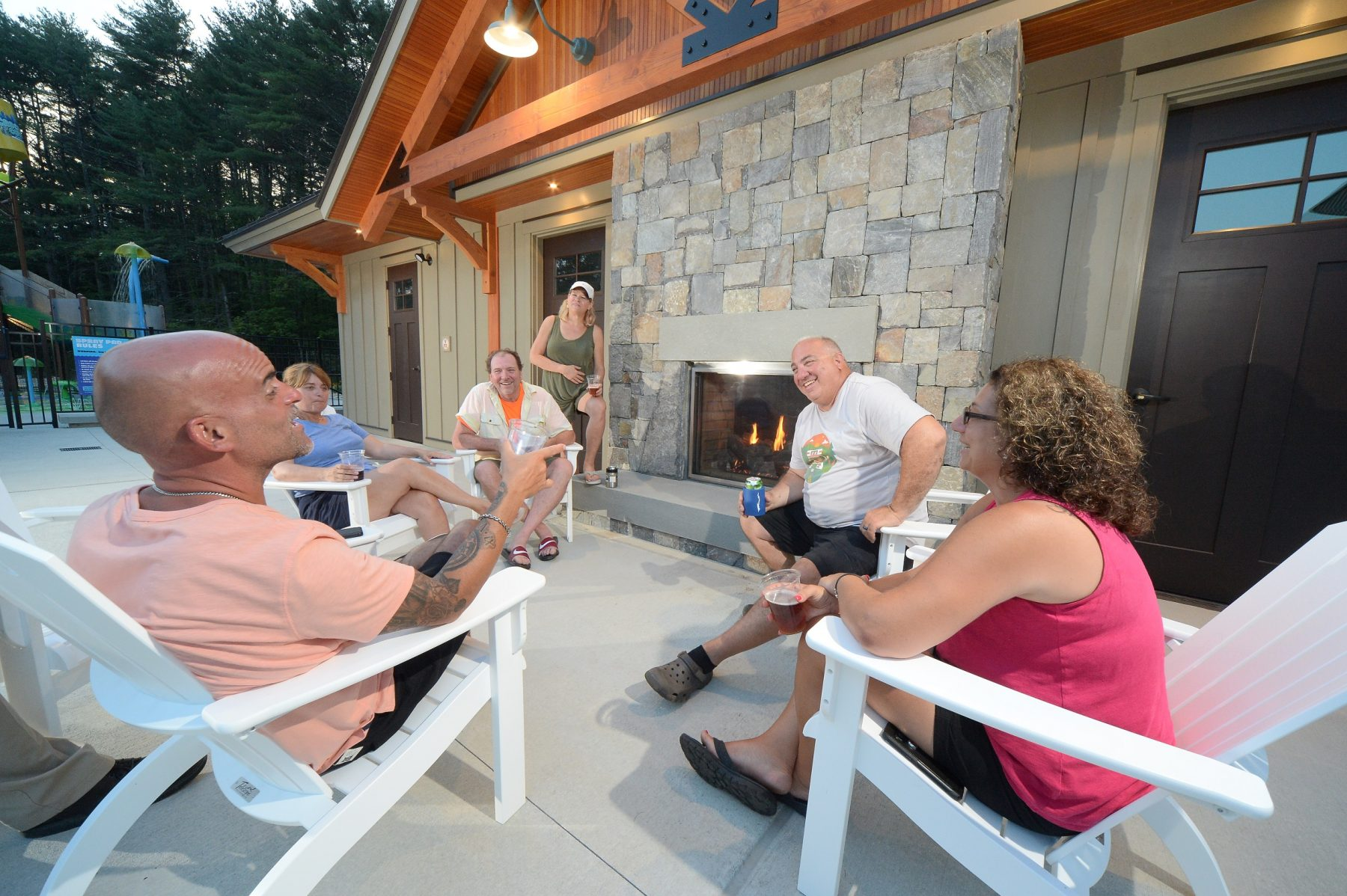 Guests are seated around and in front of a stone fireplace that is built into the wall. In the background of the photo a portion of the splash pad is shown.
