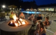 In the foreground of the photo there is six people sitting around the stone bonfire pit. There is a fire burning in the pit. In the background the zero entry pool is lit for night swimming and has many guests swimming in it. In the center of the back of this photo the slide and dump bucket of the splash pad area can be seen along with the east building.