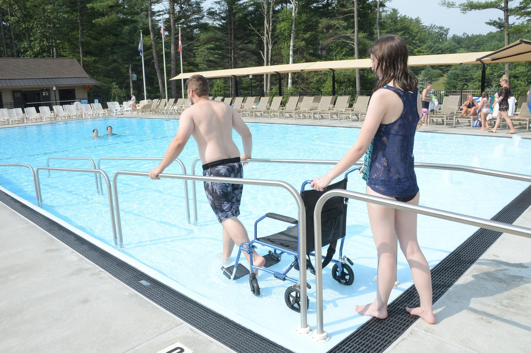 In the foreground of the photo there is a man entering the pool using the ramp. A young woman is following behind him pushing a wheel chair down the ramp into the pool. There are other guests shown swimming in the pool. To the right in the back corner of the photo other guests are shown sitting by the pool.