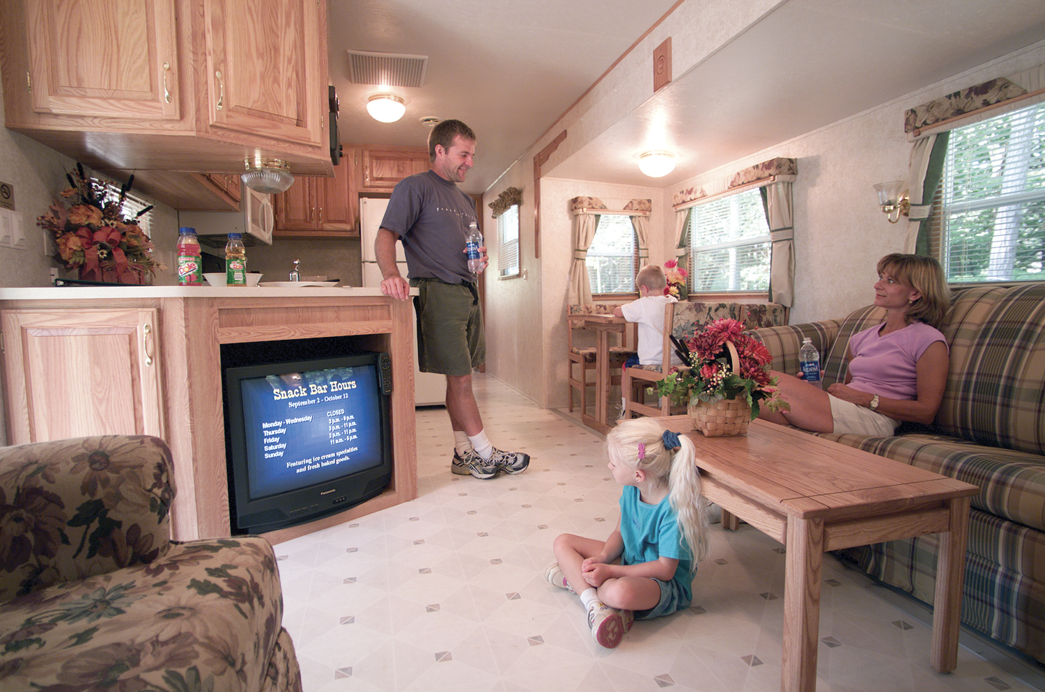 Family hanging out inside RV trailer