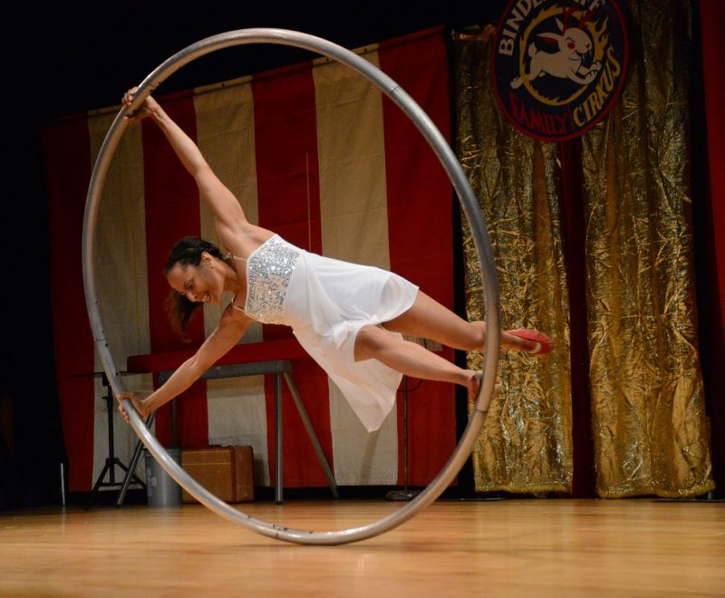 Performer holding onto large ring