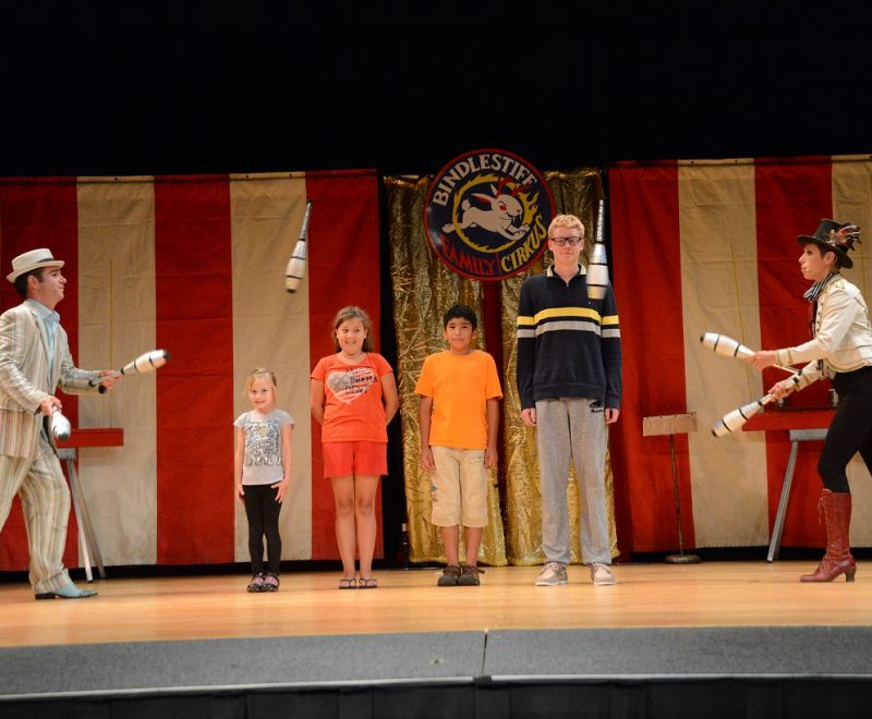 Volunteers onstage with juggling performers