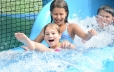 In the foreground of the photo two young girls are seen sliding down to the bottom of the slide laughing and smiling.  Behind them is a young boy being splashed by the girls in front of him.